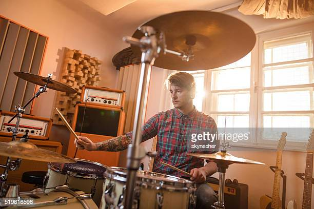 Young drummer in music studio playing drums.