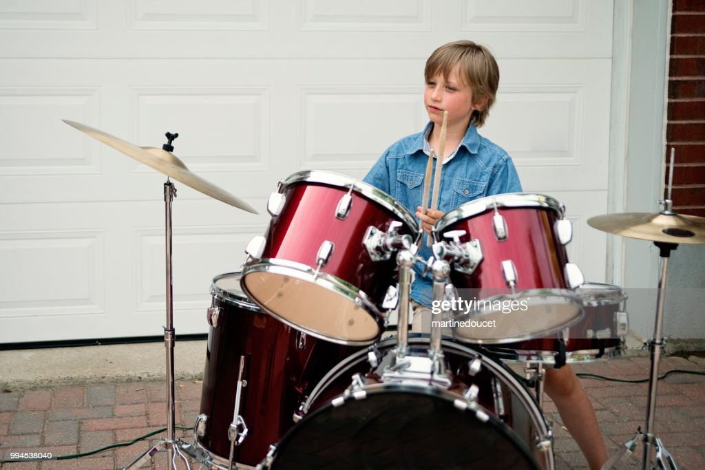 Young drummer rehearsing before show in family driveway. : Stock Photo