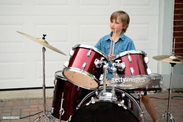 Young drummer rehearsing before show in family driveway.