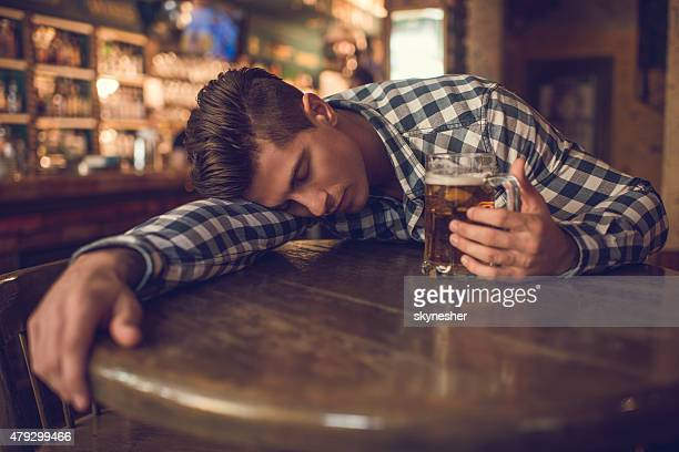 Young drunk man sleeping in a bar.