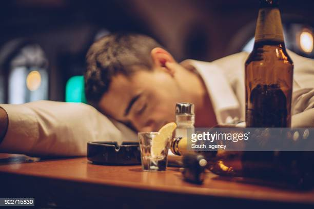 young drunk man sleeping on bar counter - binge drinking stock photos and pictures