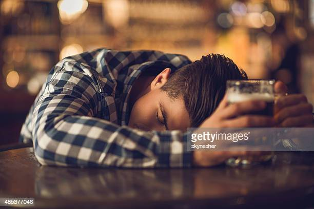 young drunk man sleeping on the table in a bar. - binge drinking stock photos and pictures
