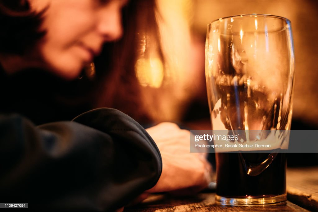 Young drunk woman drinking on bar counter drinking dark beer : Stock Photo