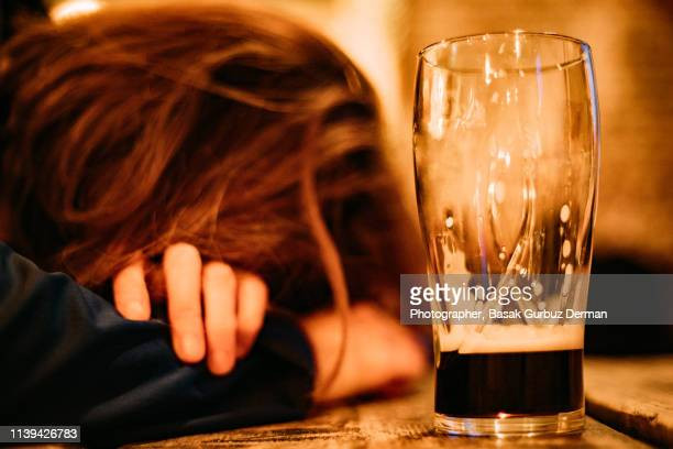 young drunk woman sleeping on bar counter drinking dark beer - drunk woman stock pictures, royalty-free photos & images