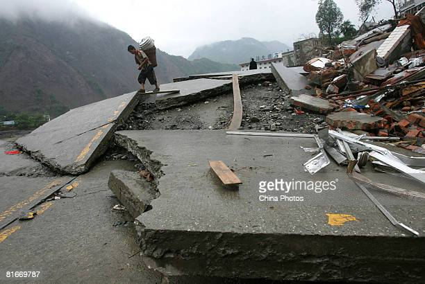A young earthquake survivor carrying a boiler walks on a broken road on June 22 2008 in Beichuan County of Sichuan Province China The evacuated...
