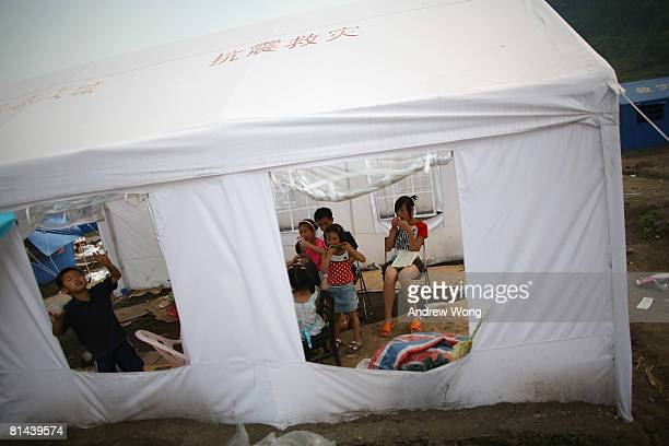 Young earthquake survivors eat fruit and ice cream in a tent at a refugee camp on June 5, 2008 in Shifang, Sichuan province, China. More than 69,000...
