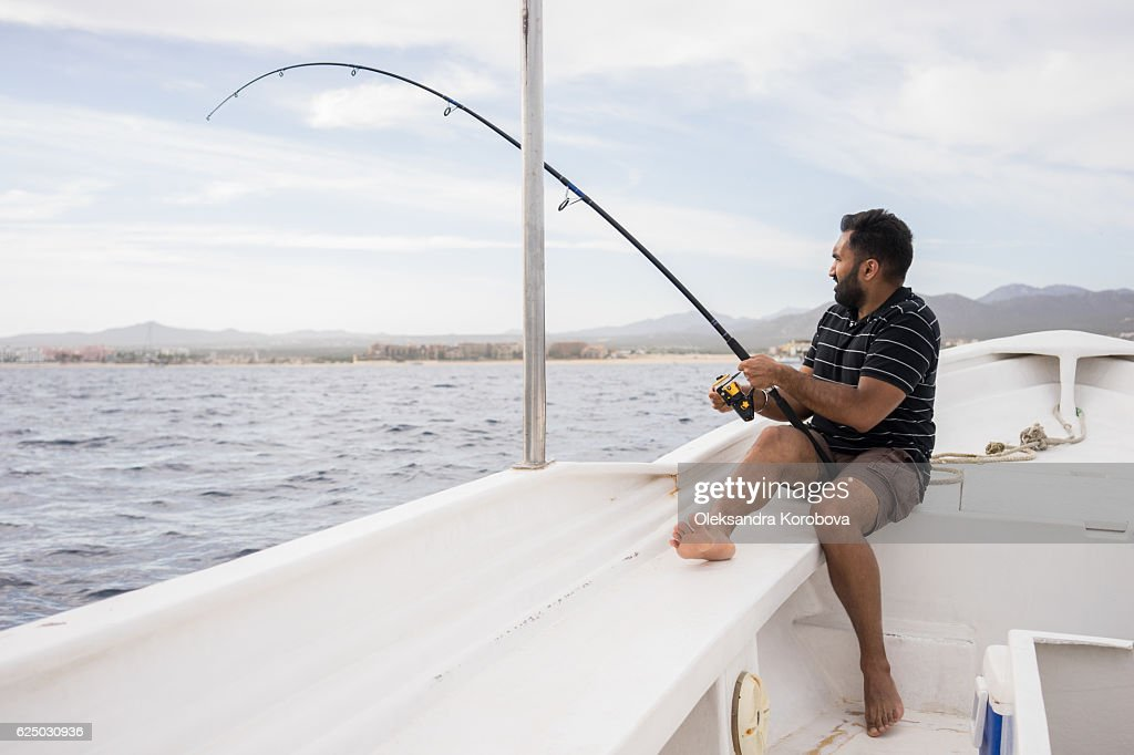 Young East Asian man fishing on open water from the boat.