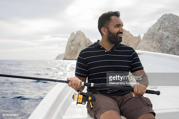 young east asian man fishing on open water from the boat. - baja east stock pictures, royalty-free photos & images