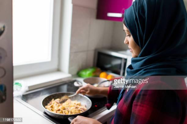 young east asian woman making breakfast - zurückhaltende kleidung stock-fotos und bilder