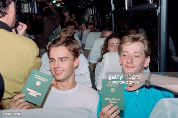 Young East German refugees wave their new West German passports from bus as they quit Bavaria refugee camp in Federal Republic of Germany for their...