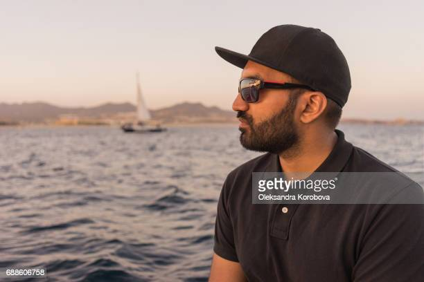 young east indian man fishing on open water from the boat at sunset. - baja east stock pictures, royalty-free photos & images