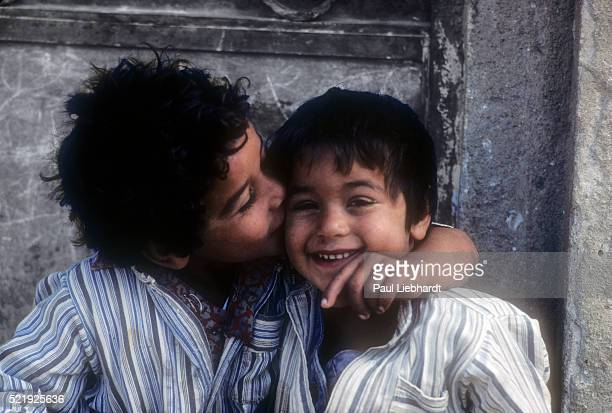 A young Egyptian boy kisses and hugs his younger brother