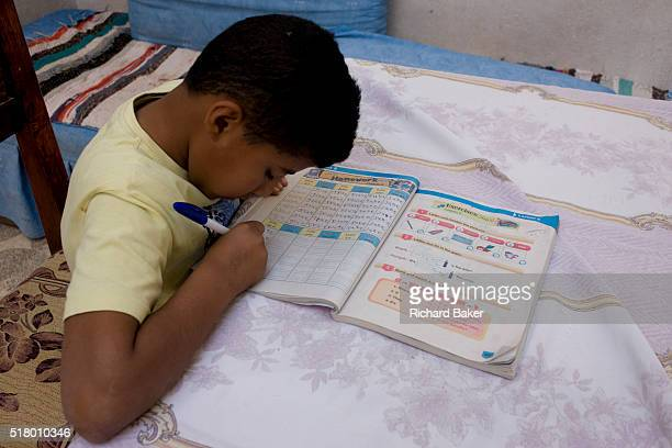 A young Egyptian boy practices his English words from a textbook at his home in the village of Bairat on the West Bank of Luxor Nile Valley Egypt In...