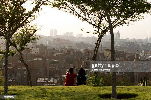 Young Egyptian couple watches the sun set on Al-Azhar park in Cairo, Egypt.
