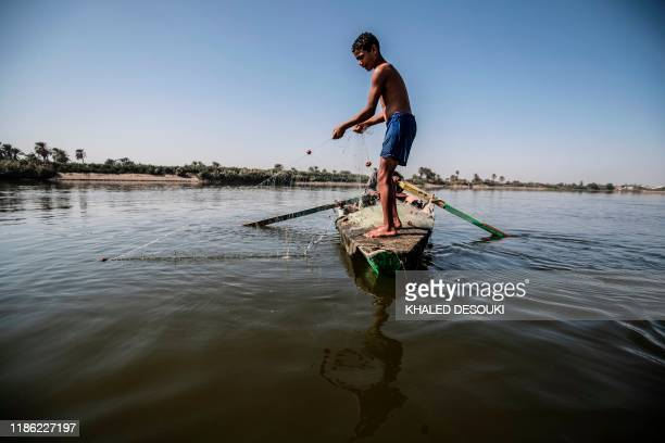 Young Egyptian fisherman pulls his net in the River Nile in Gabal al-Tear village near Minya city, some 265 km south of the Egyptian capital Cairo,...