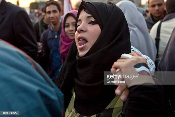 A young Egyptian woman follows the celebrations on the Tahrir Square February 12 2011 in Cairo Egypt Protesters have begun the cleanup of Tahrir...