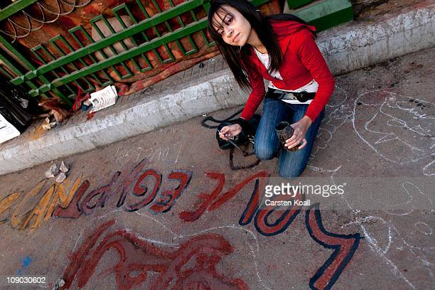 A young Egyptian woman paints the slogan 'Love Egypt' on the ground at the celebrations at Tahrir Square February 12 2011 in Cairo Egypt Protesters...