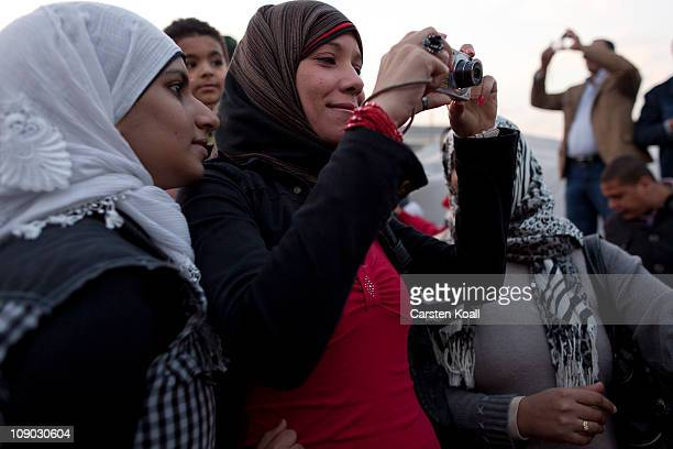 A young Egyptian woman photographs the celebrations at Tahrir Square February 12 2011 in Cairo Egypt Protesters have begun the cleanup of Tahrir...