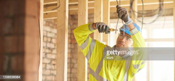 young electrician on construction site - young adult stock pictures, royalty-free photos & images
