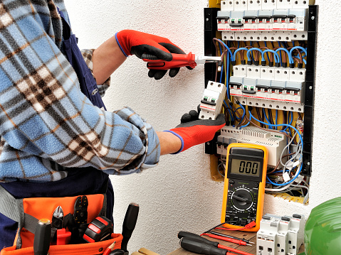 Young electrician technician at work on a electrical panel with protective gloves 904951632