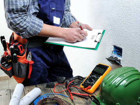 Young electrician working in a residential electrical installation 901478508