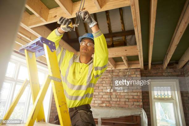 young electrician working on a remodel - ladder stock pictures, royalty-free photos & images