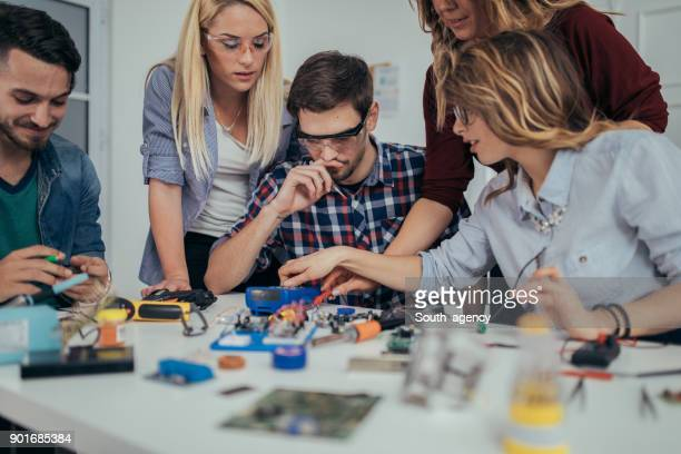 Young electronic students working on project
