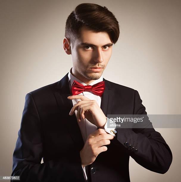 Junge elegante Geschäftsmann-Fixierung seine Manschettenknöpfe