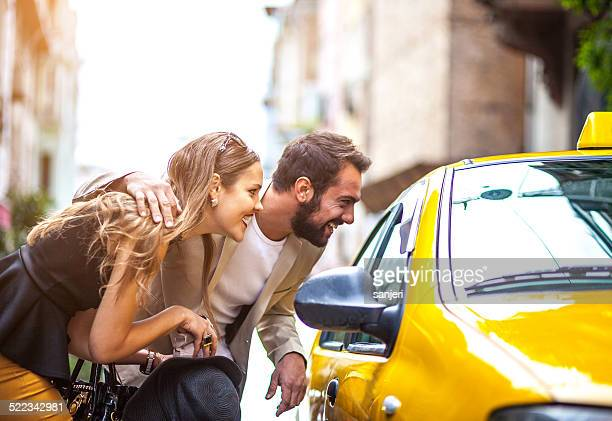 Young elegant couple taking taxi on the street