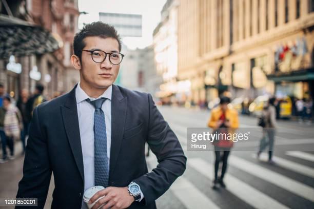 若いエレガントな男は、テイクアウトのコーヒーを持っています - 脱・男らしさ ストックフォトと画像