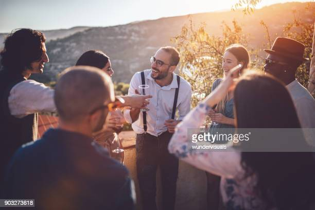 young elegant multi-ethnic friends drinking wine at countryside cottage party - eleganza foto e immagini stock