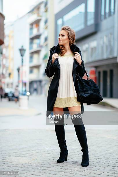 young elegant woman wearing dress and black coat - stiefel stock-fotos und bilder