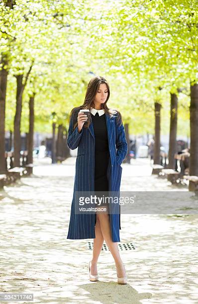 Young Elegant Woman With A Coffee Cup In A Park