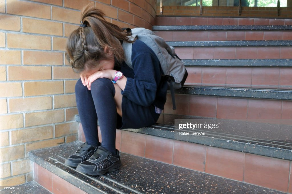 Young elementary school girl crying : Stock Photo