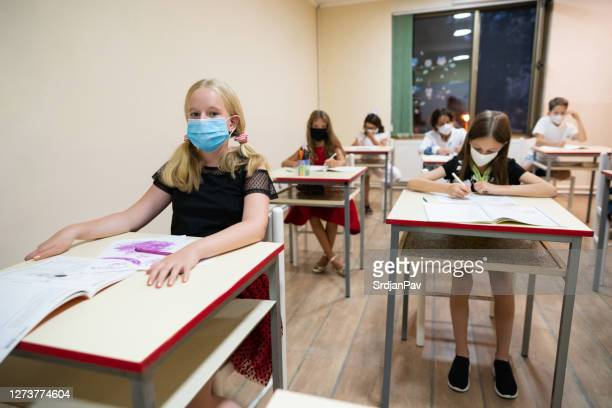 junge grundschüler im klassenzimmer tragen schützende gesichtsmasken - grundschule stock-fotos und bilder
