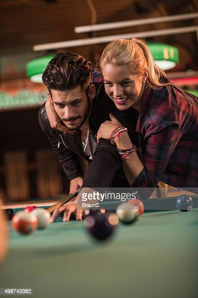 Young embraced couple playing billiard in a pool hall.