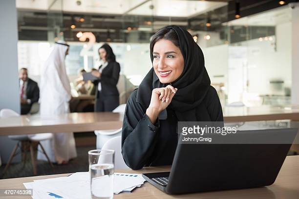 young emirati businesswoman looking away at conference table - middle east stock pictures, royalty-free photos & images