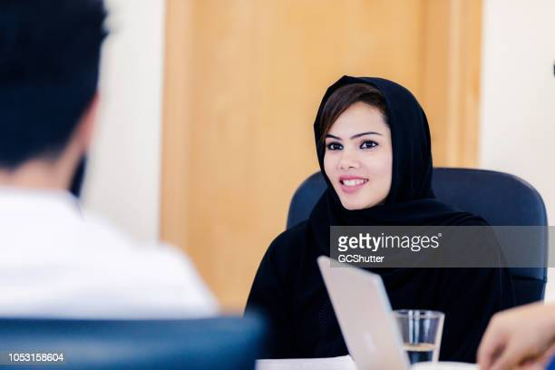 young emirati woman leading a business meeting - chairperson stock pictures, royalty-free photos & images