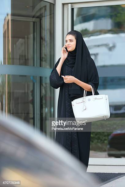 Young Emirati Woman Talking on Cellphone in Front of Hotel
