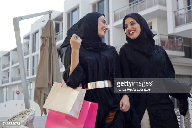 young emirati women walking with shopping bags. - kuwait national day stock pictures, royalty-free photos & images