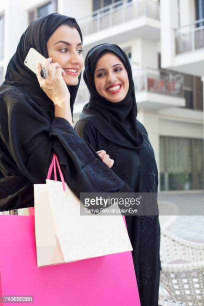 Young Emirati women walking with shopping bags.