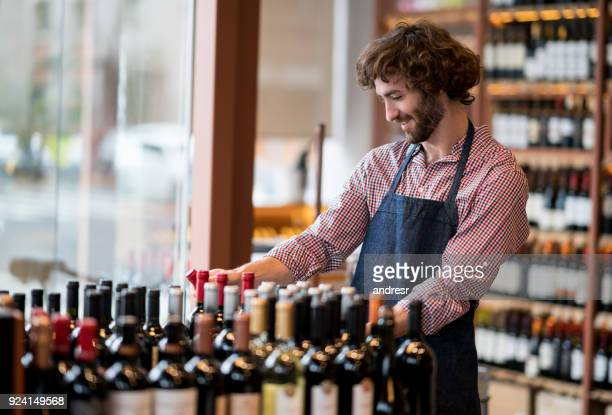 young employee at a wine store organizing the bottles on a stand looking happy - delicatessen stock pictures, royalty-free photos & images