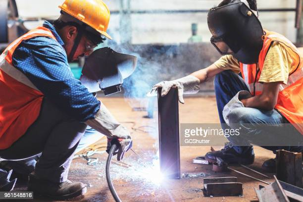 Young employee holding the metal steady as the senior welds it with another piece