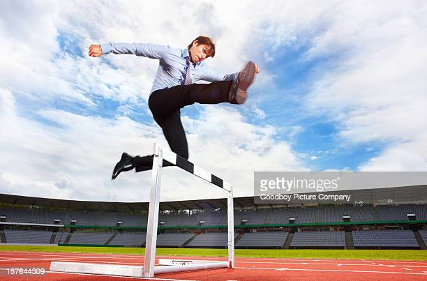 Young energetic business executive jumping over the hurdle