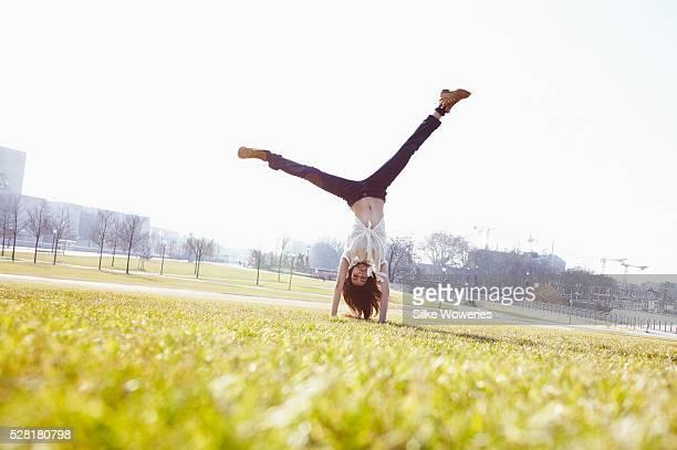 Young energetic woman doing cartwheel on lawn