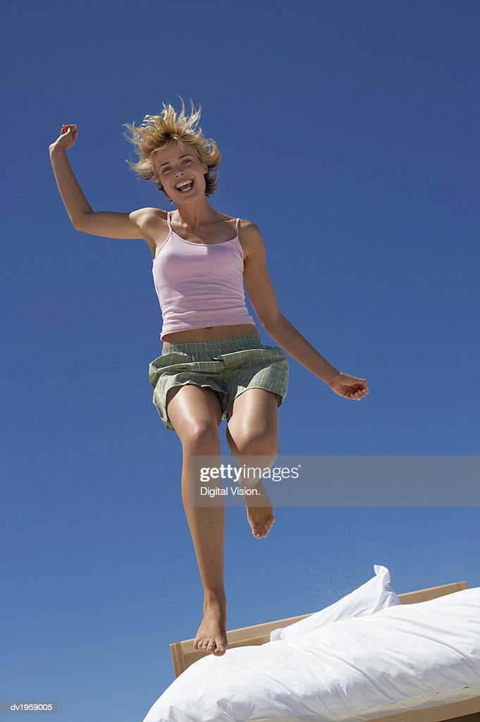 Young Energetic Woman Outdoors Jumping Out of Bed : Stock Photo