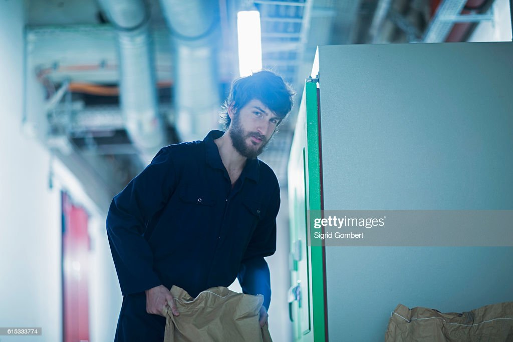 Young engineer carrying sack in an industrial plant, Freiburg im Breisgau, Baden-Württemberg, Germany : ストックフォト