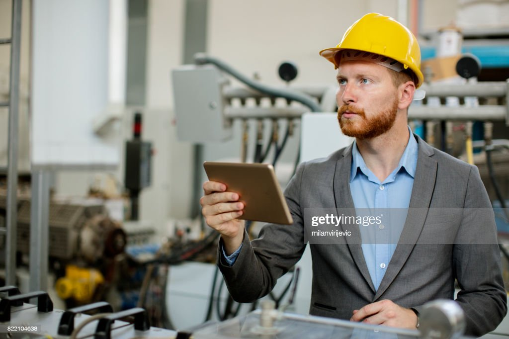 Young engineer checking machine balance in factory : Stock Photo