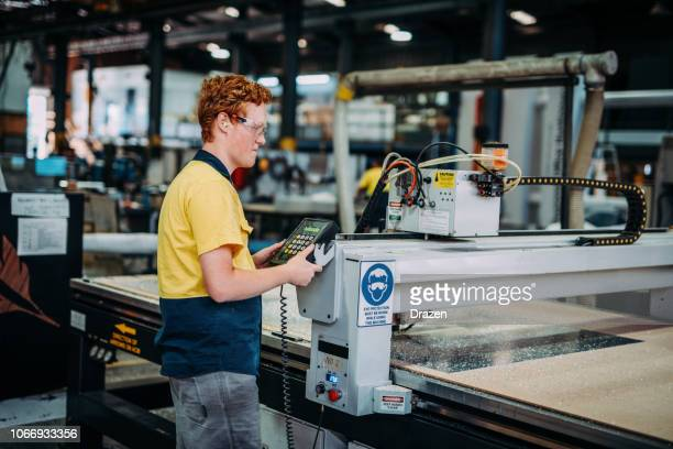 young engineer checking the cnc machine process - manufacturing stock pictures, royalty-free photos & images