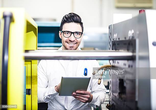 Young engineer holding digital tablet in the factory